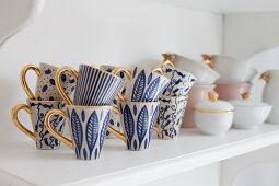 Blue-patterned mugs with gilt handles on shelf