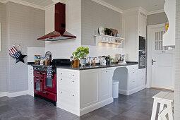 Große Landhausküche mit weißen Kassettenfronten und rotem Küchenofen