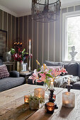 Pink lilies and arrangement of candles on coffee table in living room