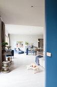 Blaue Schiebetür zum offenen Wohnraum mit Sofa und Esstisch
