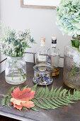 Blätter von Ahorn und Farn auf dem Tisch mit Blumen und Spiritousen