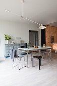 Verschiedene Stühle um einen Esstisch vor der Küche aus Sperrholz