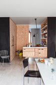 Tisch vor offener Einbauküche mit Fronten aus Sperrholz