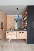 Offene Einbauküche mit Fronten aus Sperrholz und Kochinsel