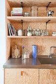 Offene Regale über der Spüle in einer Einbauküche aus Sperrholz