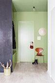 Eingangsbereich in Grün mit Garderobe als Raumteiler