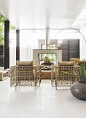 Designer rattan furniture, fireplace and arc lamp in bright interior