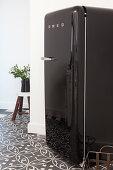 Black retro fridge on patterned floor tiles