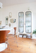 Collection of vases in old glass-fronted cabinet in retro dining room
