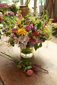 Colourful summer flowers in glass vase on wooden table