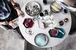 Frau sitzt am runden Marmortisch mit Geschirr und Orchidee