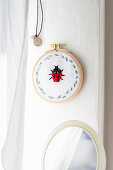 Fabric embroidered with ladybird in embroidery frame