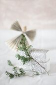 Gift wrapped in pages of book with fir sprig