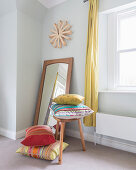 Brightly striped cushions on and next to stool in front of mirror