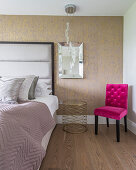 Hot-pink upholstered chair next to bed with upholstered headboard