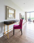Hot-pink upholstered chair at console table with gilt frame below mirror