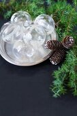 Glass Christmas-tree baubles on silver platter next to conifer branches and pine cones