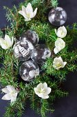Glass Christmas-tree baubles, green conifer branches and hellebore flowers