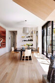 Bright dining room in designer style with wooden floor and window front