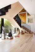 Sculpture collection on the light wooden floor under the stairs