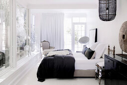 Double bed and armchair in spacious bedroom with window front