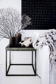 Metal side table with vintage vase next to a sofa bed