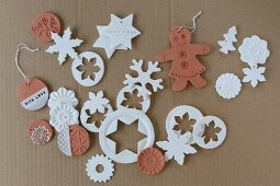 Clay Christmas decorations in white and terracotta on cardboard