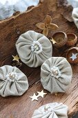 Small fabric rosettes with beads and gold stars on piece of bark