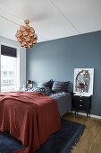 Red bedspread on bed against blue-grey wall