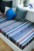 Gemusterte Matratze auf einem Tagesbett am Fenster