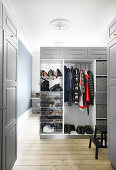Half-open wardrobe with grey doors used as partition