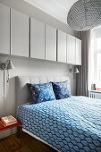Grey, wall-mounted cupboards above bed with blue-patterned bed linen