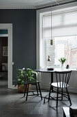 Black table and two chairs below window in grey wall