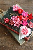 Origami flowers in various shades of red and pink on old books