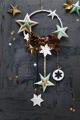 Weihnachtsdeko an einem Ring mit Sternen und Zapfen