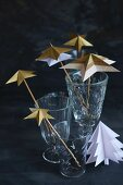 Arrangement of paper stars threaded on rods in glasses on table