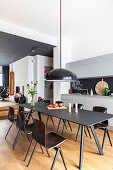 Black, modern dining set in open-plan kitchen of designer loft apartment