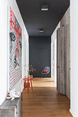 Black ceiling and wall and wooden fitted cupboards in hallway