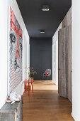 Flur mit schwarzer Decke und Wand und einem Einbauschrank aus Holz