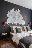 Map of Berlin on black wall above bed