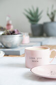 Pink cup with lettering on set table