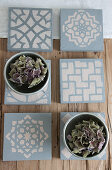 Hand-made, concrete-effect tiles with stencilled patterns