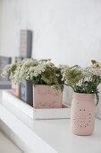 Mit Kreidefarbe bemalte Glasgefäße als Pflanzenbehälter