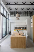 Wooden dining table attached to island counter in loft-apartment kitchen with glass wall