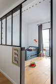 Letter E on half-height partition wall with interior windows screening child's bedroom