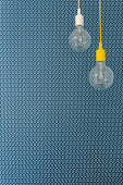 Two pendant lamps in front of blue patterned wallpaper