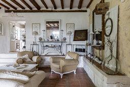 Beigefarbene Sessel und Couch in rustikalem Wohnraum mit gemauerter Ablagefläche, Terrakottafliesenboden und Holzbalkendecke