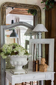 Flowers in urn, bust, picture frame and table lamp on console table in front of mirrors