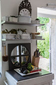 Crockery on shelves, mirror, knife block and vegetables on chopping board in rustic kitchen
