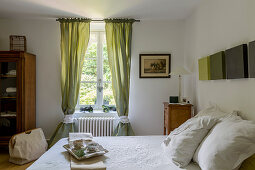 Breakfast tray on double bed and antique bedside cabinet in rustic bedroom with green curtains